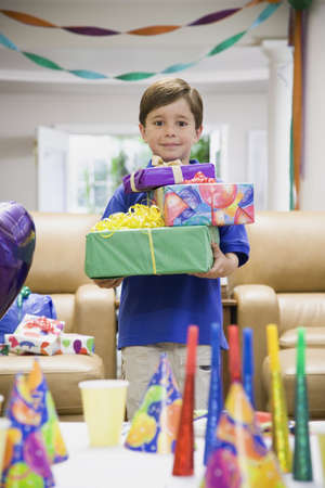 attired: Boy holding stack of gifts at party