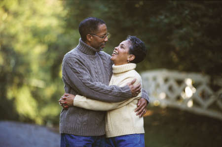 boomers: Senior African couple hugging outdoors