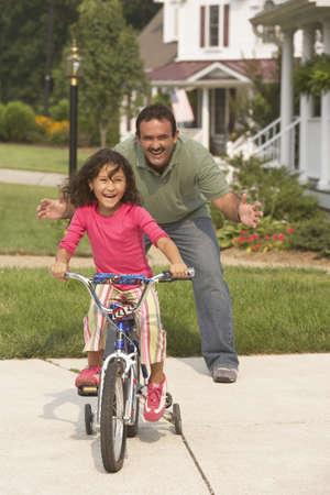 babyboomer: Hispanic father helping daughter ride bicycle LANG_EVOIMAGES