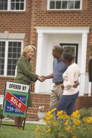 south western european descent: African couple shaking hands with real estate agent LANG_EVOIMAGES