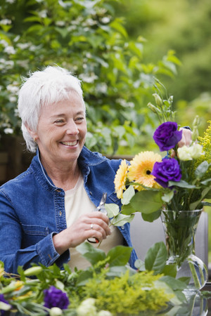 Senior woman smiling and arranging flowers in vase Stock Photo