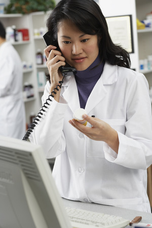 connexion: Asian female pharmacist talking on telephone