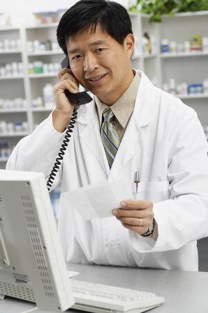talker: Asian male pharmacist talking on telephone