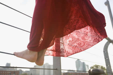 pj's: Close up of womans bare feet standing on railing