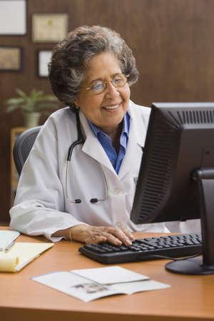 doctor computer: Senior Hispanic female doctor using computer at desk LANG_EVOIMAGES