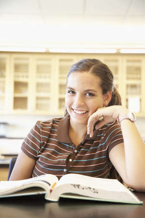 Teenaged girl with text book in classroom Stock Photo