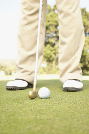 interrogating: Close up of golfer putting on green