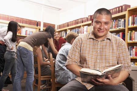 teenaged boy: Teenaged Hispanic boy smiling with book in library