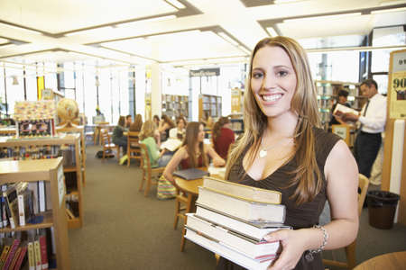 teenaged girl: Teenaged girl smiling with stack of books in library