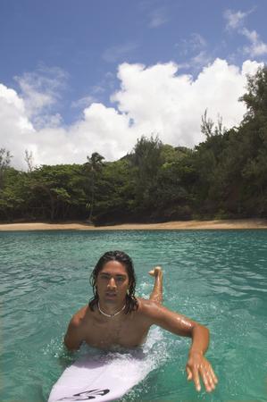 attired: Pacific Islander man paddling surfboard in water