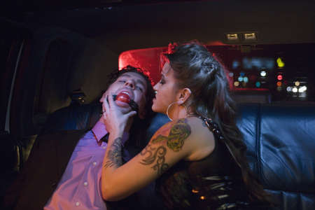 Dominatrix and man wearing ball gag in limousine