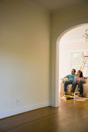 Hispanic couple with painting supplies in new home Stock Photo