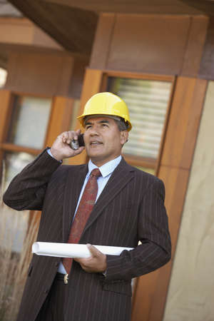 babyboomer: Hispanic businessman with hard hat and blueprints using cell phone LANG_EVOIMAGES
