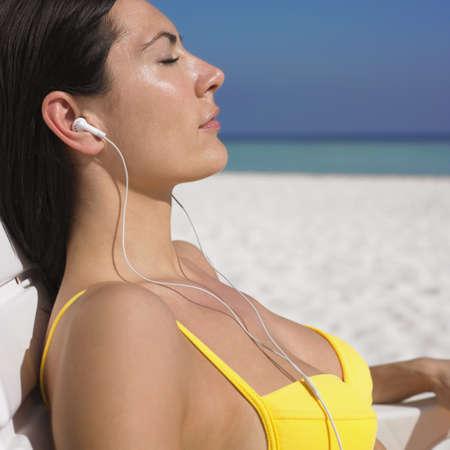 nite: Woman listening to headphones at beach