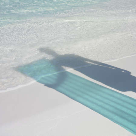 honeymooner: Shadow of person holding pool raft at beach