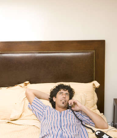 Man laying on bed talking on telephone