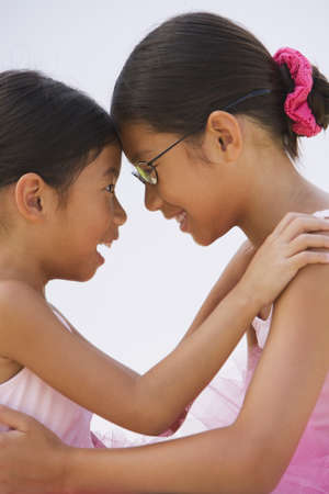 outfits: Asian sisters in ballet outfits hugging LANG_EVOIMAGES