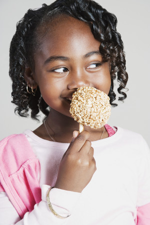 candy apple: African girl eating candy apple LANG_EVOIMAGES