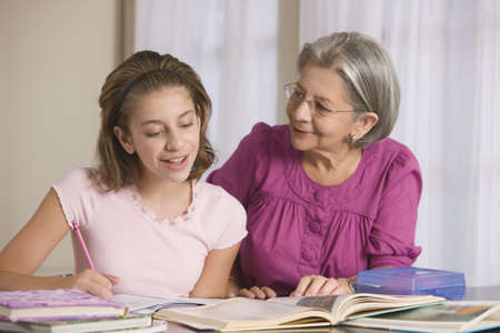 generation gap: Hispanic grandmother helping granddaughter with homework LANG_EVOIMAGES