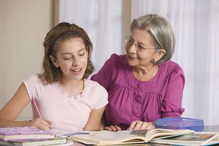 gramma: Hispanic grandmother helping granddaughter with homework LANG_EVOIMAGES