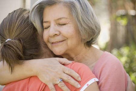 adoring: Hispanic grandmother hugging granddaughter