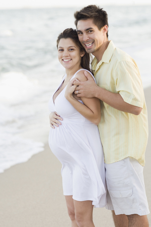 Husband hugging pregnant wife on beach Banco de Imagens