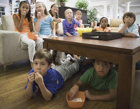 connexion: Children eating popcorn in livingroom LANG_EVOIMAGES