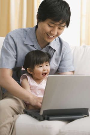 poppa: Asian father and baby daughter looking at laptop