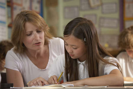 cooperating: Teacher helping student at desk