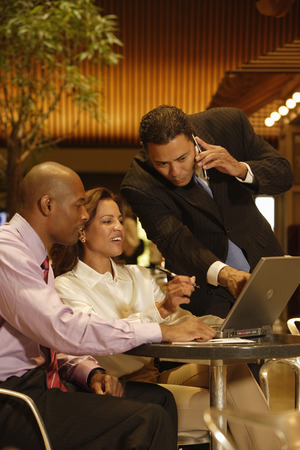 teleworking: Multi-ethnic businesspeople looking at laptop