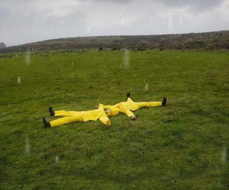 drizzling rain: Hispanic couple in rain gear laying in grass