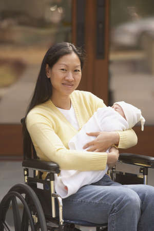 sopping: Asian mother in wheelchair with newborn baby