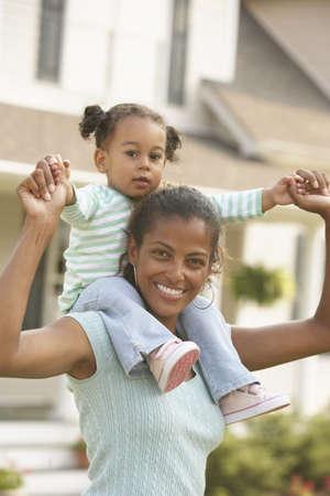 flogging: African mother holding daughter on shoulders LANG_EVOIMAGES
