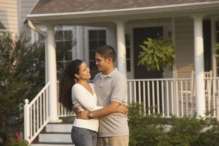 solicitous: Hispanic couple hugging in front of house LANG_EVOIMAGES