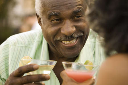 laughter: Senior African man smiling with cocktail LANG_EVOIMAGES