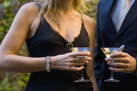 gramma: Close up of couple in fancy clothing holding martinis LANG_EVOIMAGES