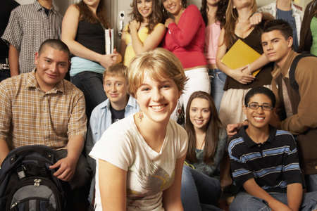 teenaged girl: Teenaged girl smiling in front of group of students