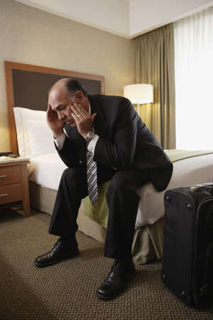 motioning: Middle-aged businessman sitting on bed in hotel room
