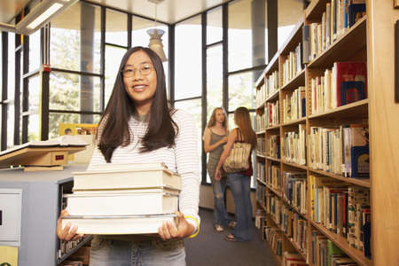 teenaged girl: Teenaged Asian girl carrying books in library