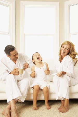 Hispanic family laughing on sofa LANG_EVOIMAGES