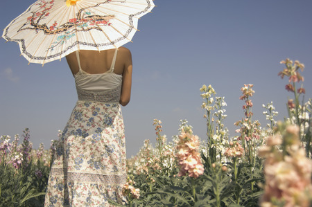 getting away from it all: Rear view of Asian woman holding parasol LANG_EVOIMAGES