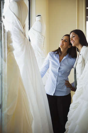 coming home: Hispanic sisters looking at wedding dresses in shop
