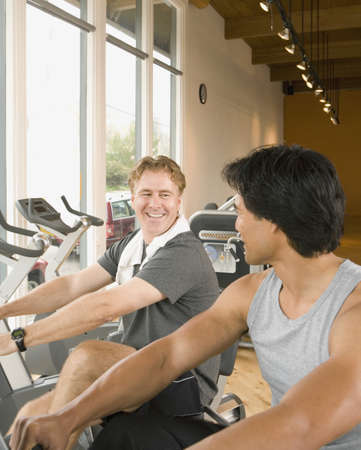 spectating: Two men using exercise bikes in health club