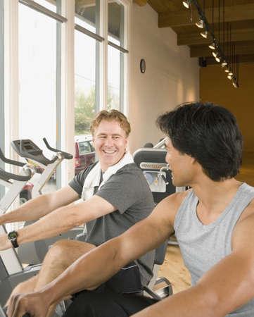 handtruck: Two men using exercise bikes in health club