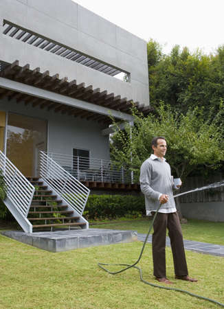 tugging: Man watering lawn in front of house LANG_EVOIMAGES