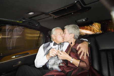 dinner wear: Well dressed senior couple kissing in limousine LANG_EVOIMAGES