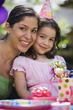 eveningwear: Hispanic mother and daughter at outdoor birthday party