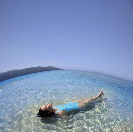 islander: Pacific Islander woman laying in ocean LANG_EVOIMAGES
