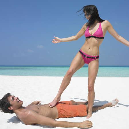 receding hairline: Woman standing on boyfriend at beach