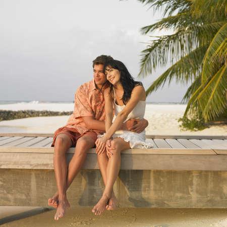 seventy two: Couple sitting on beach boardwalk